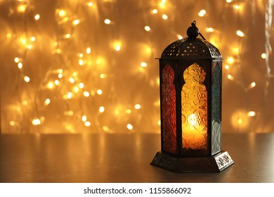 Muslim lamp with candle on table against blurred fairy lights. Fanous as Ramadan symbol