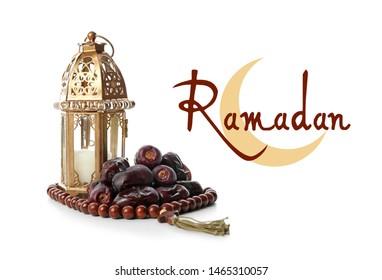 Muslim lamp, dates, tasbih and word RAMADAN on white background