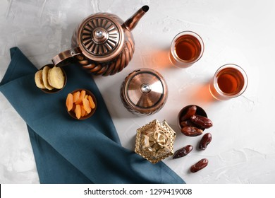 Muslim lantern with dried fruits and tea on light table