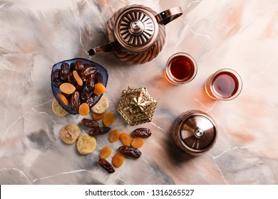 Muslim lantern with dried fruits and tea on table