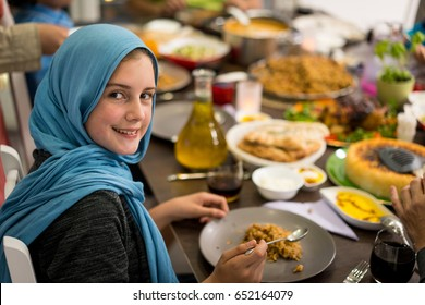 Muslim little girl having dinner at home with her family