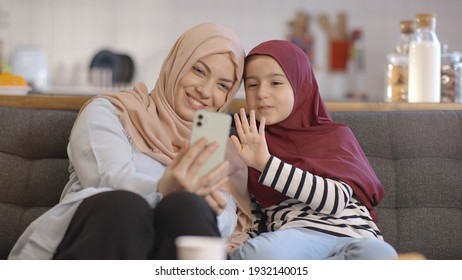 Muslim little girl and her mother cheerfully video chat over the phone.