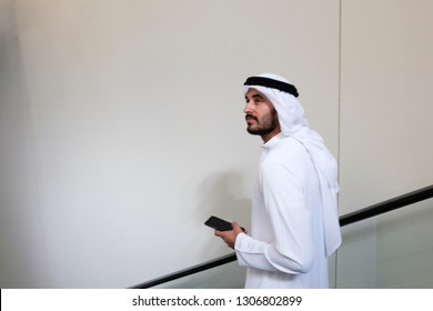 Muslim local man on a vertical escalator holding a mobile phone device