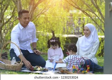 muslim malay family enjoying picnic at the park