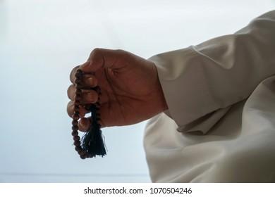 A Muslim Man hand holding rosaryor tasbih. Symbolize praise to god.