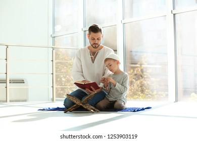 Muslim man and his son reading Koran together indoors