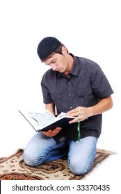 Muslim man is holding holly book Qoran and praying on traditional way