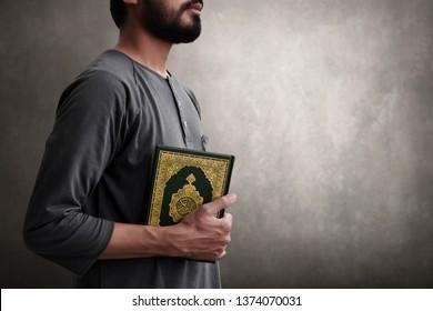 Muslim man holding koran