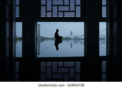 A muslim man pray at mosque with reflection and framing