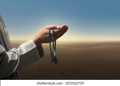 Muslim man pray with prayer beads over blue sky background