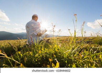 Muslim man praying outdoor. Sunrise and nature landscape.