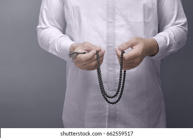 Muslim man praying with prayer beads over dark background