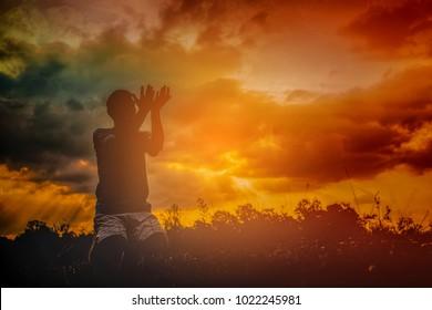 Muslim man praying at sunset on the mountain