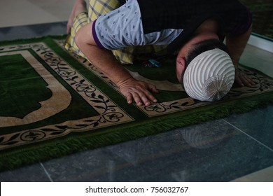 A Muslim man put his head on the floor while he is perform his prayer / sujud