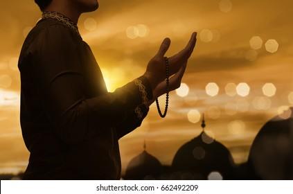 Muslim man raising hand and praying with prayer beads during sunset background
