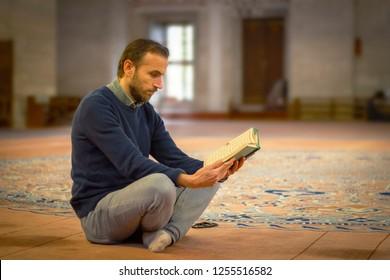 Muslim man reading holy book (Qur'an)