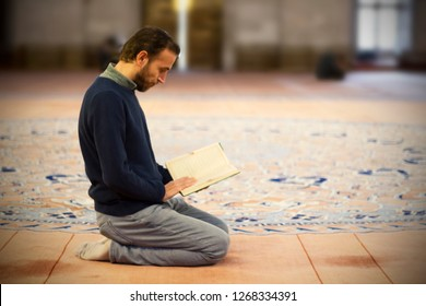 Muslim man reading Holy Book (Qur'an) in mosque
