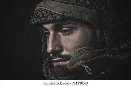 Muslim man with a sad face with a beard in a military jacket and a national headdress kufia on a black background