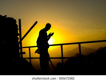 """A muslim man in silhouette while pray at the peak of Mount Al-Nour or  """"jabal al-nur"""" a place whereby Hira cave is located."""