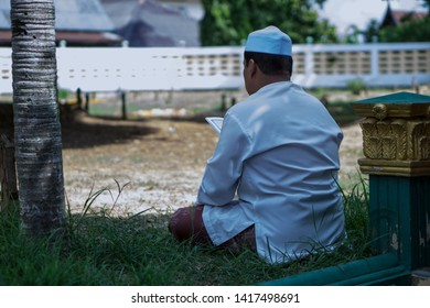 Muslim man sitting in Kubor tomb of Islamic for reading Al-Quran for The deceased