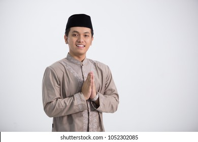 A muslim man stand and pose in front of the camera