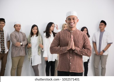 A muslim man standing in front of a group in studio