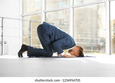 Muslim man in suit praying on rug indoors