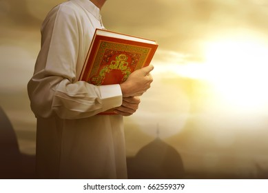 Muslim man in traditional dress holding holy book Koran during sunset background