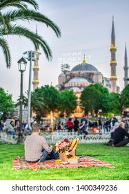 Muslim man waiting for iftar in Sultanahmet Square. Blue Mosque is seem on background. Picnic in Istanbul. Young man enjoying summertime in Istanbul, Turkey.