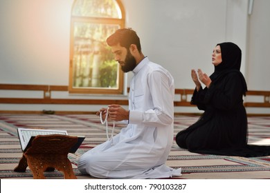Muslim man and woman praying in mosque