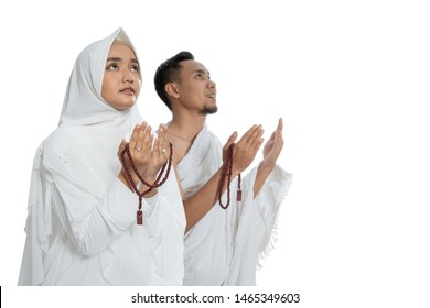 Muslim man and woman praying while standing in white traditional clothes ihram isolated over white background