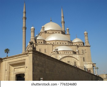 Muslim mosque with minaret on blue sky background in sand. Beautiful mosque of sandy color against blue sky, sunny day. Mosque on sand of the citadel Salah El-Din, Cairo, Egypt