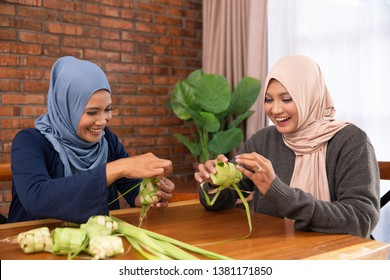 muslim mother and daughter making traditional ketupat or rice cake at home for eid mubarak