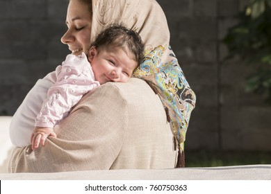 Muslim mother embraced a newborn baby in outdoor environment