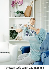 Muslim mother playing with her newborn baby boy over white background.