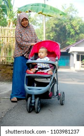 a muslim mother pushed her baby sitting in a stroller