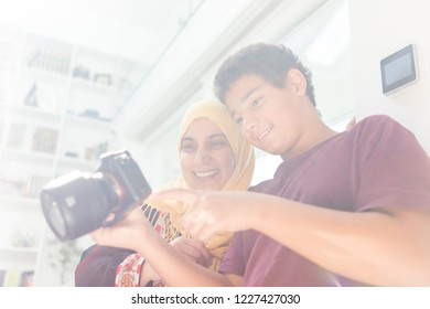 Muslim mother and son reviewing photographs on camera