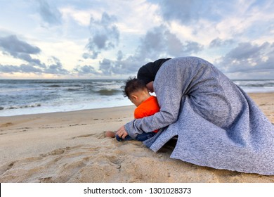 Muslim mother and son sit playing at beach in the evening. Back view.