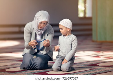 Muslim mother teach her son praying inside the mosque