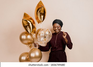 Muslim new year party with golden balloons for black woman. African attractive girl celebration of the end of year. Happy emotion