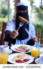 muslim niqab woman eating breakfast delicious food with orang juce and tea at restraurant