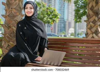 Muslim office worker sitting ouside. Arab woman looking in the camera and smiling.