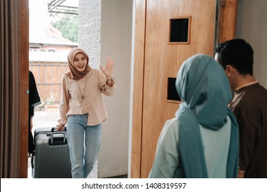 muslim people visiting friend and family on eid mubarak. hari raya balik kampung concept. people shake hand apologizing each other