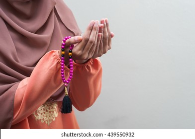 A Muslim person wearing traditional malay clothes with hijjab and rosary, praying in the mosque, Muslim woman raising hand pray