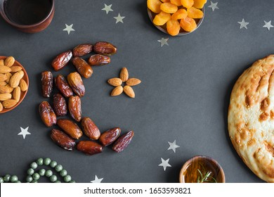 Muslim Ramadan Kareem with dates fruits arranged in shape of crescent moon, water and bread on black background, top view. Iftar food or Iftar party concept.