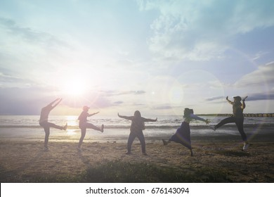 Muslim relative group of happy young people dancing and spraying at the beach on beautiful summer sunset.