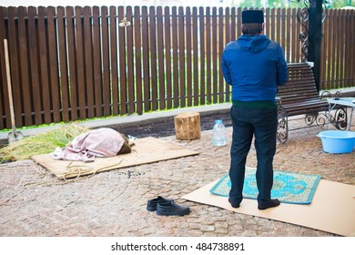 Muslim religious Mullah prays after ritual killing sheep on holiday Kurban Bairam