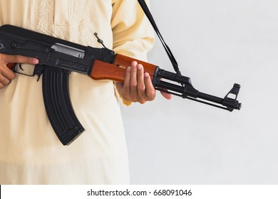 Muslim Robber holding a gun at abandoned building. Low key photo and selective focus. criminality concept.