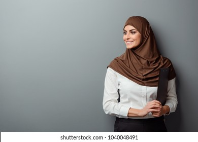 Muslim student holding folder with documents and smiling. Half-length portrait with copy space.