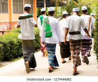 Muslim Students in traditional-made batiks and white round skullcaps;taqiyah, were going to school